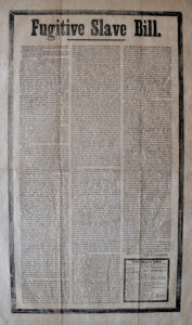 """An old, yellowed, creased sheet of long paper with """"Fugitive Slave Bill"""" printed at the top, and three long columns of text beneath"""